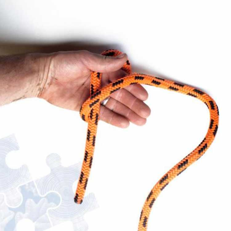Orange rope showing second step of creating a Fishermans knot