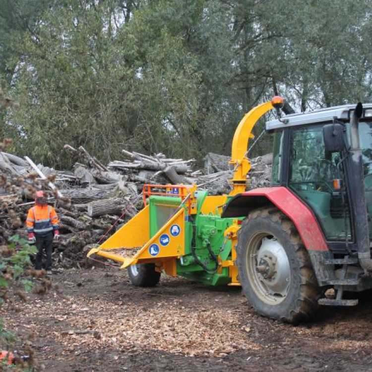 Red tractor with a yellow Heizohack 8-400 Chipper attached to the back operating on site on a winters day