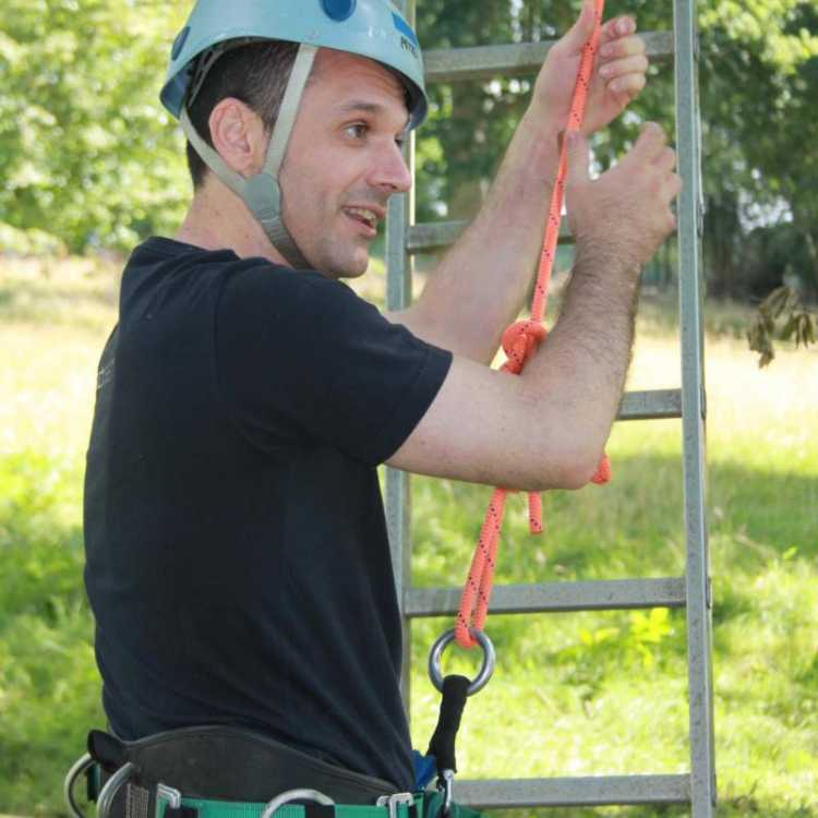 Man with his climbing gear on holding a ladder
