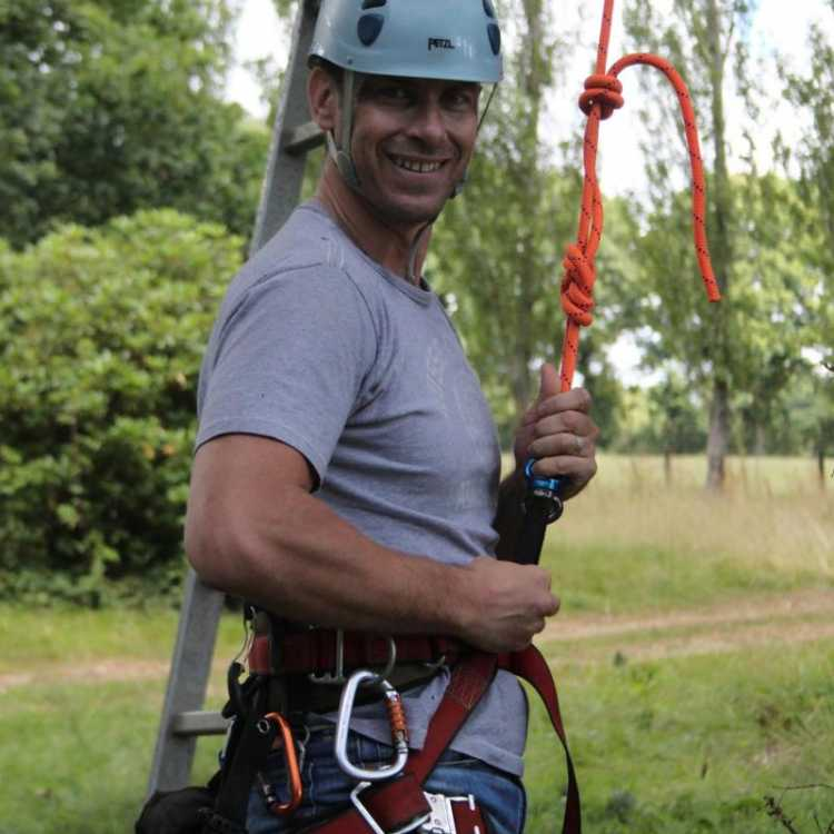 Man wearing his gear about to start tree climbing