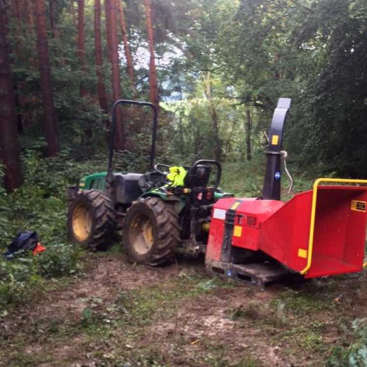 A Red TP160 Chipper being transported on site by a small green tractor