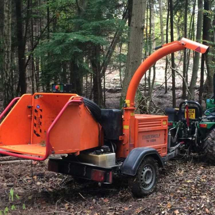 An Orange Timberwolf Chipper being transported on site by a small green tractor through a wooden area