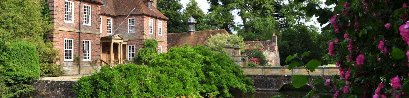 The beautiful Groombridge Place House surrounded by vibrant green trees, water